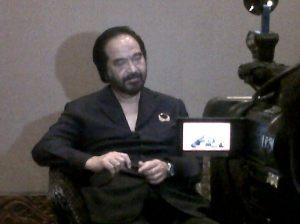 Surya Paloh saat wawancara live dengan Kompas TV. Gaya busana khas.