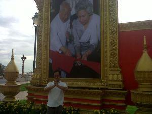 Di depan baliho pasangan mendiang Norodom Sihanouk dan Ratu Monineath. Negara pengimpor minyak.